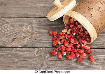 Wild strawberries spilled from the basket