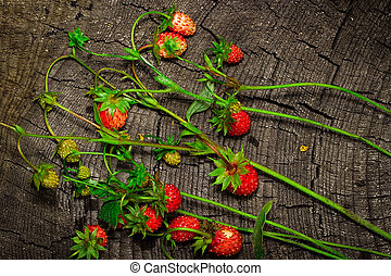 Wild strawberry on a wooden background