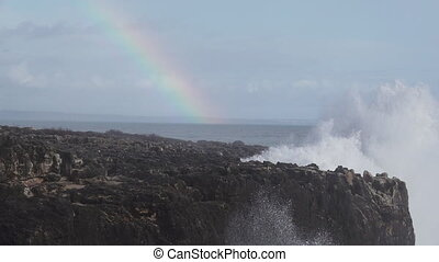 Wild waves breaking in the atlantic coast with rainbow in...