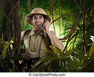 Young retro explorer having a phone call with vintage telephone in the jungle.