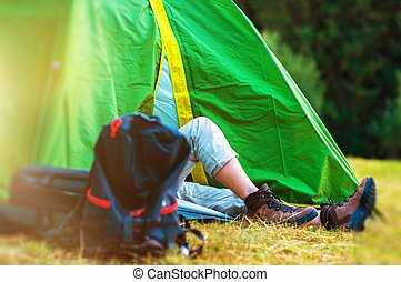 Wilderness Tent Camping. Hiker Resting in His Green Tent....