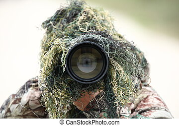 wildlife photographer using camouflage and pointing his huge 300mm 2.8 telephoto lens at you while outdoors