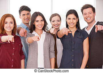 Will you join our team? Group of cheerful young people standing close to each other and pointing you