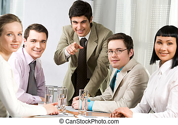 Image of friendly workteam sitting around table with their leader pointing at camera