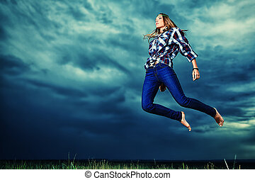 willpower - Beautiful young woman jumping in the field over...