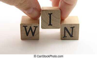 WIN blocks - Man\'s hands placing wooden blocks to spell WIN...