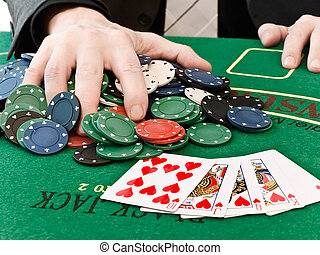 win - a man holds his hand on a large number of won chips