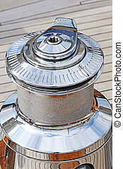 Close-up of a chromium plated winch on a wooden sailboat