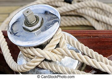 Close-up of a rope tied-up on a winch of a sailboat