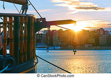 Winch with hooks on the stern of a wooden ship in the evening port with cityscape on background