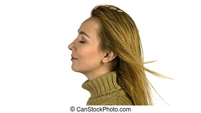 Wind blowing on woman in warm clothes - Side view of woman...