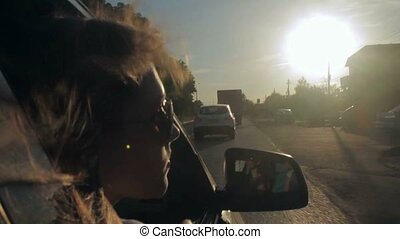 Wind Blowing Through Girl's Hair In a car with family. Sunset