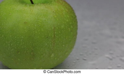 Wind blows away the drops of water from a rotating green apple.