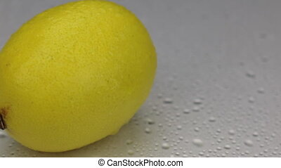 Wind blows away the drops of water from a rotating lemon.