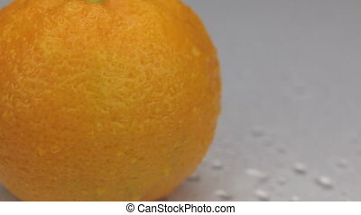 Wind blows away the drops of water from a rotating mandarin.