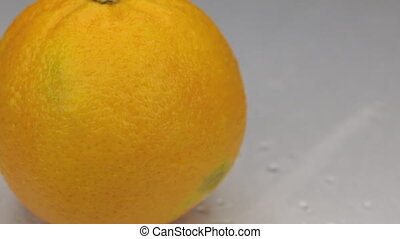 Wind blows away the drops of water from a rotating orange.