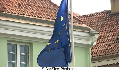 Wind blows on EU flag. Yellow stars on blue cloth. Order and...