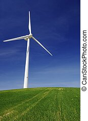 wind energy - Modern windmill on a green hill with blue sky