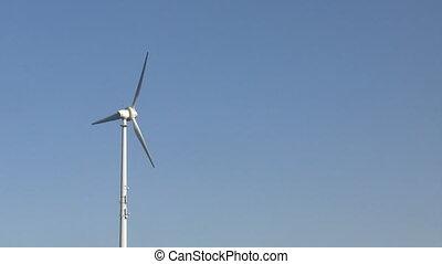 Rotating wind turbine under pure blue sky