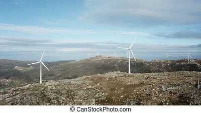 Wind energy turbines, in a landscpae over a beautiful blue sky