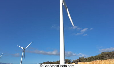 Wind energy turbines on blue sky background, sustainable...