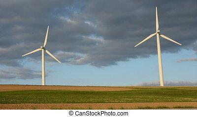 Two modern windmills rotating in high-wind