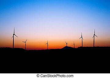 Wind farm silhouette in sunset light. Windmills.