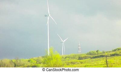 Wind farm with sky and clouds on the mountain with spring green grass