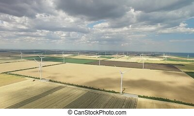 Wind farms in rural areas against the background of agricultural fields under a blue sky. Aerial survey
