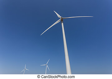 Wind generators from below, against a blue sky.