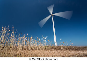 Wind generators in motion from below, grass in the foreground.