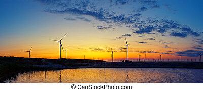 Wind generators power plant on lake at sunset