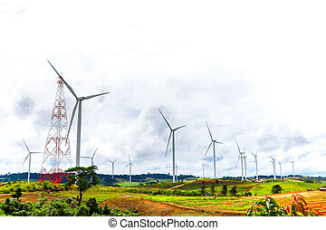 Wind generators turbines on sunset summer with mountain and blue sky landscape.