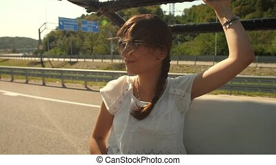 Wind playing with woman's hair at the car - Wind playing...
