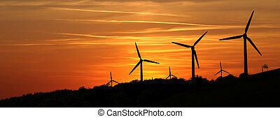 Wind power plant in the mountains at sunset