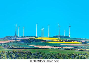 Wind power turbine generators rotate in a field