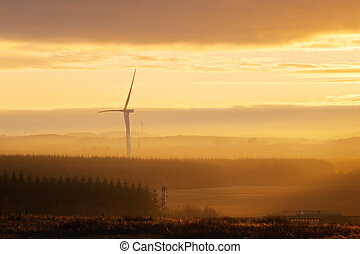 Wind power turbines in the countryside at sunset