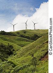 Three energy generating windmills on a green hilltop.