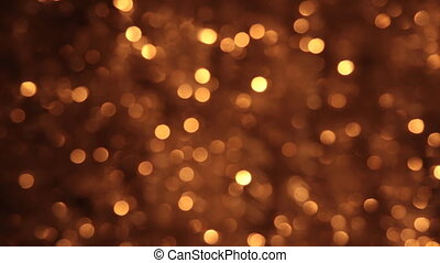 Wind shakes bokeh from gold tinsel.