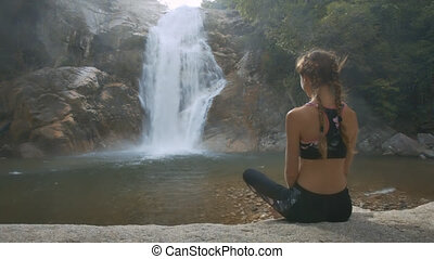 Wind Shakes Girl Plaits Sits on Stone by Waterfall - close...