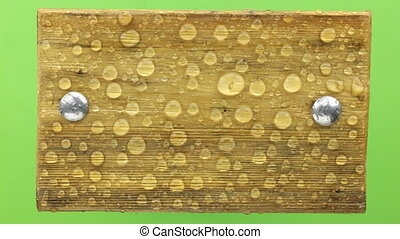 Wind shakes water drops on a wooden board with iron bolts,...