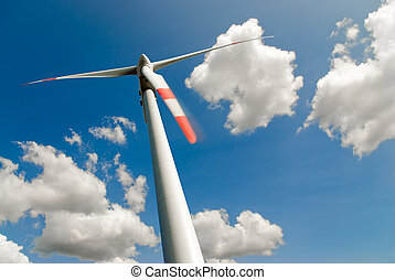 low angle view of a wind turbine against a blue sky full of white clouds
