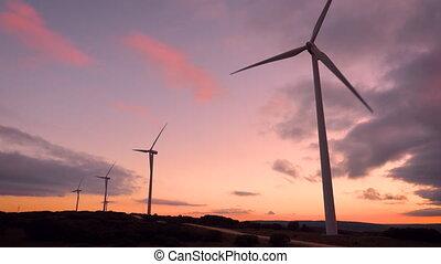 Wind turbine farm on beautiful purple sunset mountain...