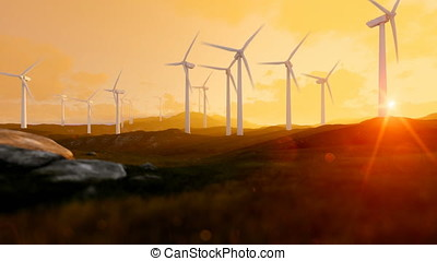 Wind turbine farm over green meadow, rays of light at sunset