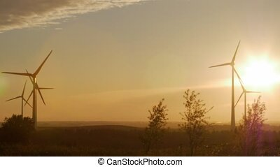 Wind turbine farm with rays of light at sunset