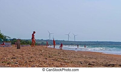 Wind turbine generators spinning on background while people have beach fun on foreground
