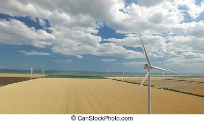 Wind turbine on a background of yellow steppe near the sea. Aerial survey