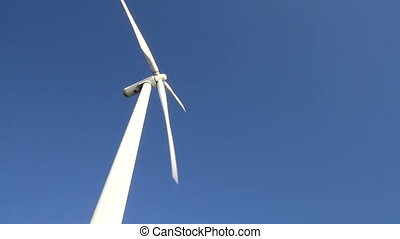 Wind turbine on blue sky - White wind turbine rotating at...