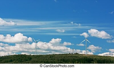 Wind turbine the mountain against bright cloudy sky