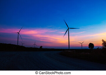 Wind turbine with the silhouette at sky.